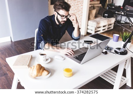 Handsome man working from his home office - stock photo
