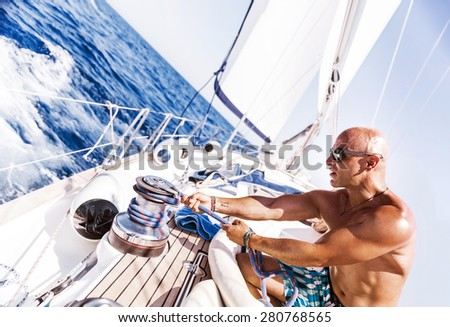 Handsome man working on sailboat, pulling rope, active summer vacation on water transport, having fun in the sea, enjoying water sport - stock photo