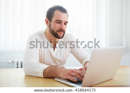 Handsome man working with laptop in the office