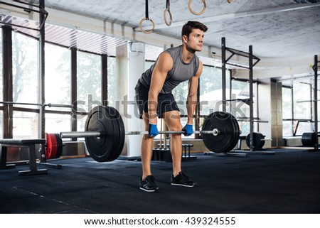 Handsome man workout with heavy barbell in gym - stock photo