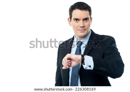 Handsome manager checking time on his wrist watch - stock photo