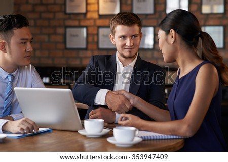 Handsome manager greeting woman at business meeting in cafe