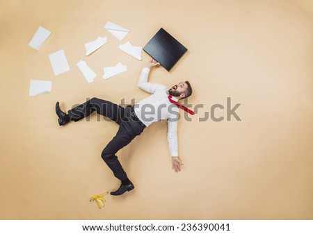 Handsome manager having an accident. Studio shot on a beige background. Funny pose. - stock photo