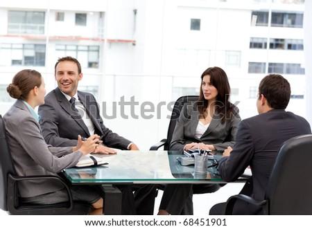Handsome manager laughing during a meeting with his team at work