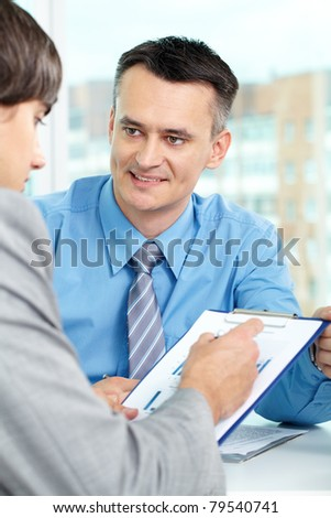 Handsome manager looking at business partner during conversation - stock photo