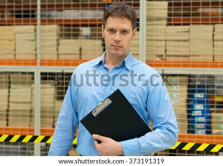 Handsome manager with clipboard in post office.