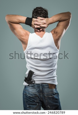 Handsome masculine criminal with hands up behind head rear view - stock photo