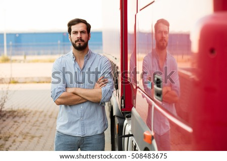handsome masculine driver with beard wearing jeans standing with folded arms next to his truck and looking with confidence at camera