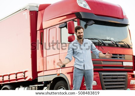 handsome masculine truck driver standing outside with his vehicle behind