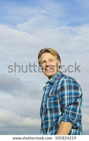 handsome mature blond man in his forties wearing a blue checked shirt against a blue sky backround - stock photo