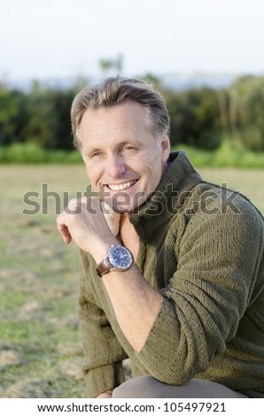 handsome mature blond man in his forties wearing a wrist watch - stock photo