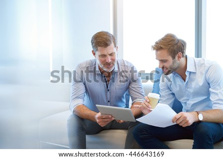 Handsome mature business manager using a digital tablet to discuss something positive with a young employee in a modern business lounge - stock photo