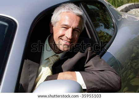 Handsome mature businessman in car - stock photo