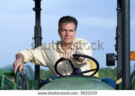 Handsome mature male sitting comfortably on a big green tractor smiling confidently. - stock photo
