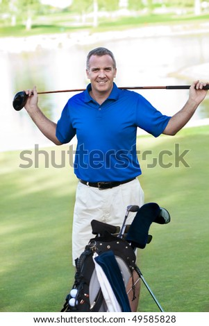 Handsome Mature Male smiling on the Golf Course - stock photo
