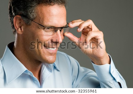 Handsome mature man holding a pair of modern glasses - stock photo