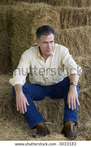 Handsome mature man sitting on some bales of hay at the end of an afternoon of working with the horses. - stock photo