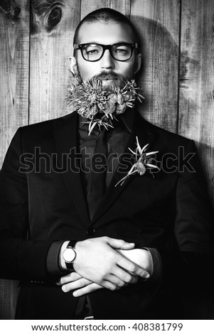 Handsome mature man with a beard of green flowers. Men's beauty. Barbershop.