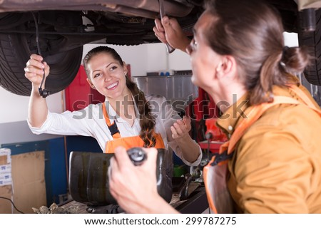 Handsome mechanic and beautiful female assistant working at the auto repair shop  - stock photo