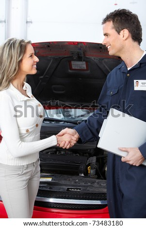 Handsome mechanic and client woman in auto repair shop. - stock photo
