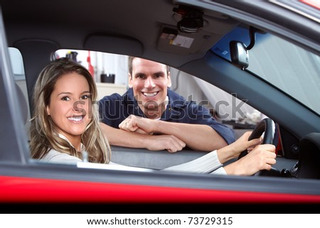 Handsome mechanic and woman in auto repair shop. - stock photo