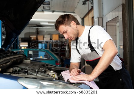 Handsome mechanic based on car in auto repair shop checking engine
