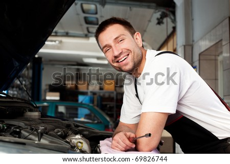handsome mechanic based on car in auto repair shop smiling - stock photo