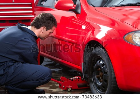 Handsome mechanic changing a tire. Auto service. - stock photo