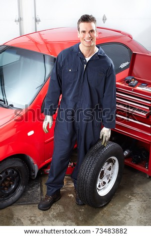 Handsome mechanic changing  wheels in auto shop. - stock photo