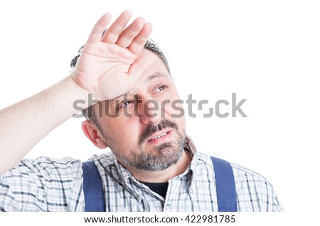 Handsome mechanic in closeup being exhausted or stressed and wiping sweat isolated on white background - stock photo