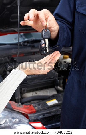 Handsome mechanic inspecting the tire pressure in auto repair shop. - stock photo