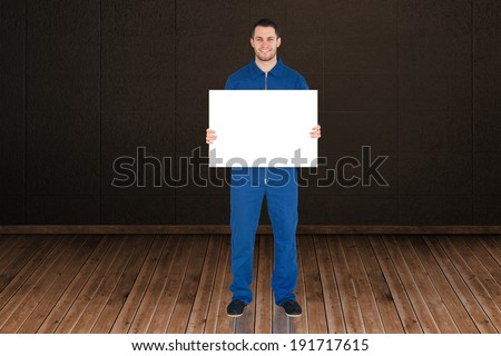 Handsome mechanic showing card against dark room with floorboards - stock photo
