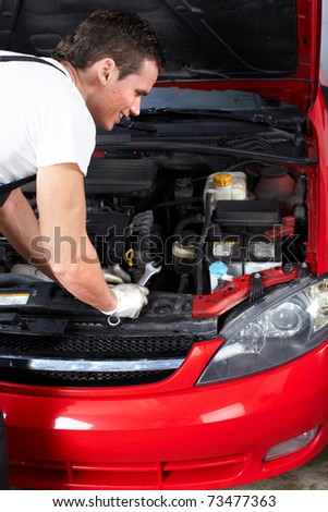 Handsome mechanic working in auto repair shop. - stock photo