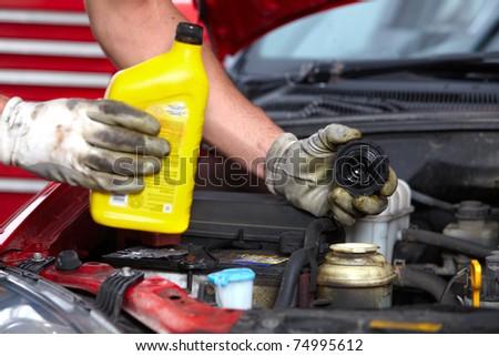 Handsome mechanic working in auto repair shop. - stock photo