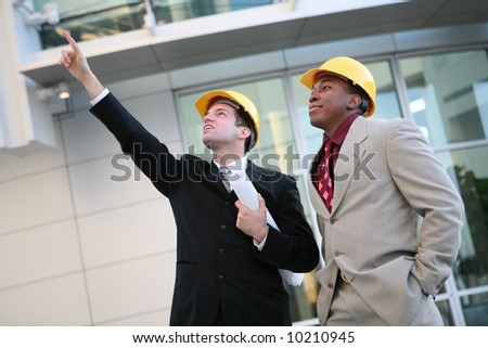 Handsome men working as architects on a construction site - stock photo