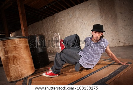 Handsome Mexican man performs break dancing moves - stock photo