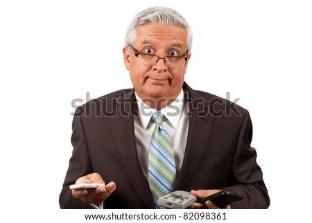 Handsome middle age business man wearing a suit and glasses holding electronic devices with a dumbfounded expression on a white background.