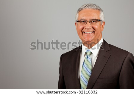Handsome middle age business man wearing a suit and glasses on a gray background.