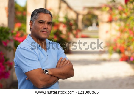 Handsome middle age Hispanic man in casual clothing outdoors. - stock photo