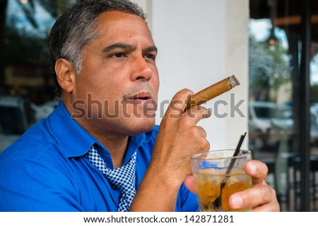 Handsome middle age Hispanic man smoking a cigar with a cocktail. - stock photo