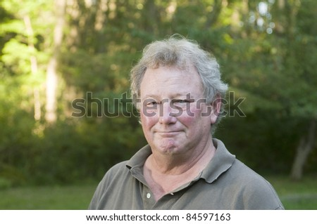 handsome middle age homeowner in suburban wooded backyard