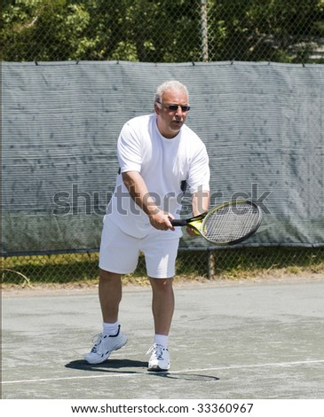 handsome middle age male tennis player hitting forehand stroke on tennis court at club - stock photo