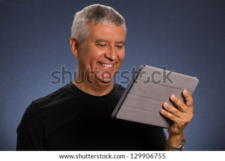 Handsome middle age man holding a tablet computer in a studio portrait. - stock photo
