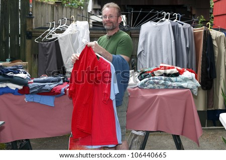 Handsome middle age man holding shirts at an outdoor tag sale with other clothes and blankets behind him.
