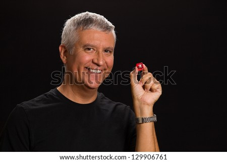 Handsome middle age man in a studio portrait holding a Las Vegas craps game dice.