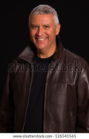 Handsome middle age man in a studio portrait wearing a leather jacket.