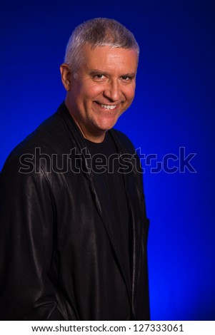 Handsome middle age man in a studio portrait wearing a leather sports coat.