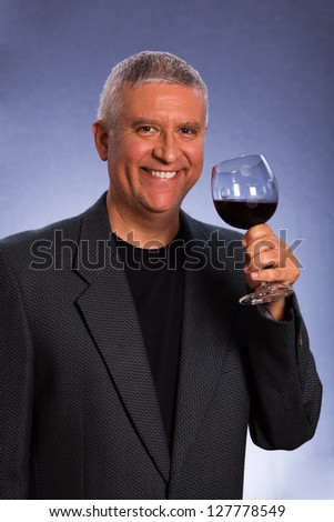 Handsome middle age man in a studio portrait with a glass of red wine.
