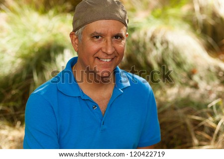 Handsome middle age man in casual clothing wearing a stylish hat outdoors.