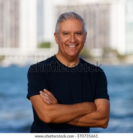 Handsome middle age man outdoor portrait with a downtown bay skyline background. - stock photo